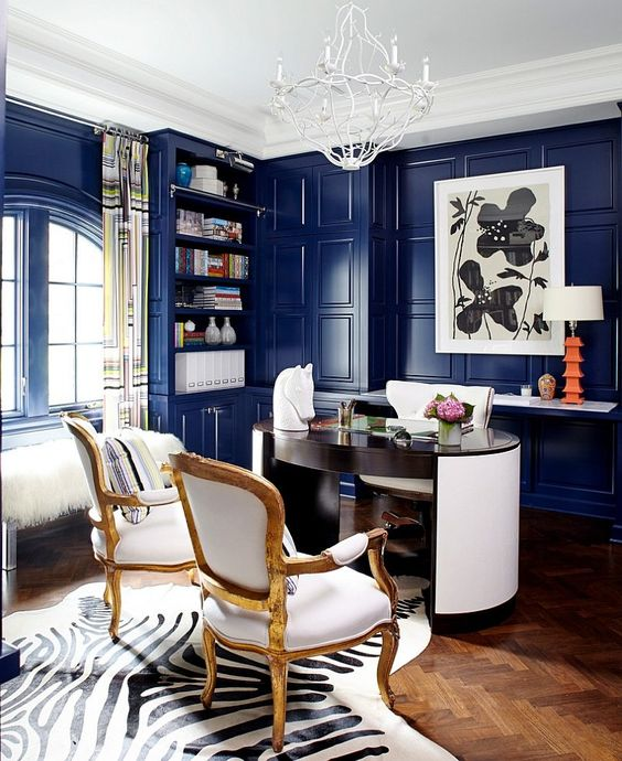a luxurious blue home office with bright walls, a round desk, white furniture, a quirky chandelier, an acrylic bench with faux fur