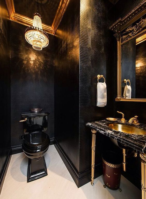 a luxurious powder room with black leather walls, a crystal chandelier, a black toilet, a black marble vanity and a gold sink
