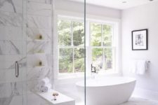 a luxurious white bathroom clad with white marble tiles and a large window for more natural light inside