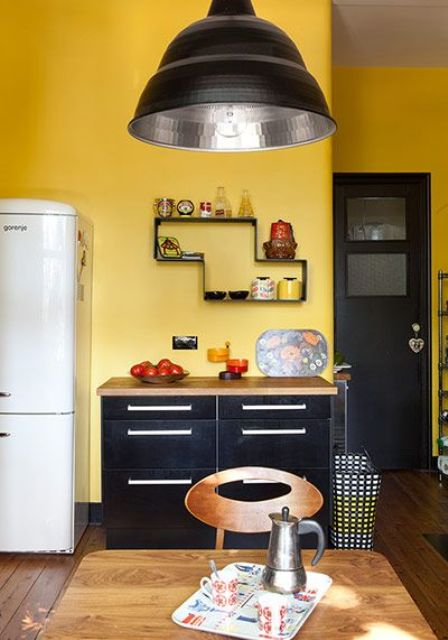 a mid-century modern kitchen with yellow walls, black cabinets, a black door and a lamp for a statement look