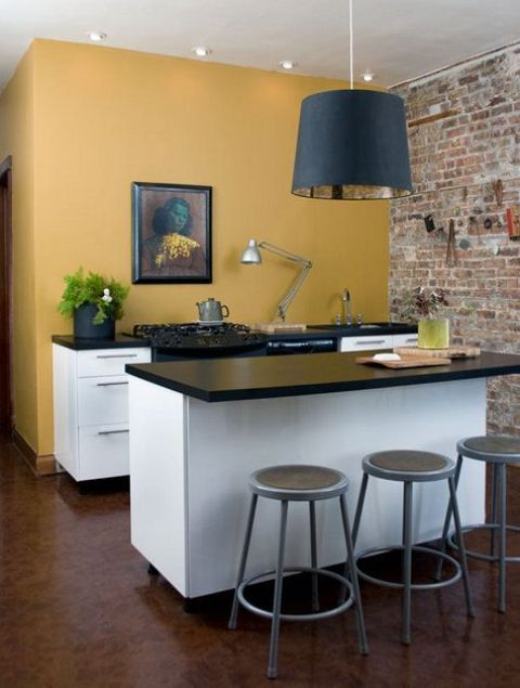 a mini kitchen space with a dark yellow wall, white cabinets, black countertops, a black pendant lamp and a vintage artwork