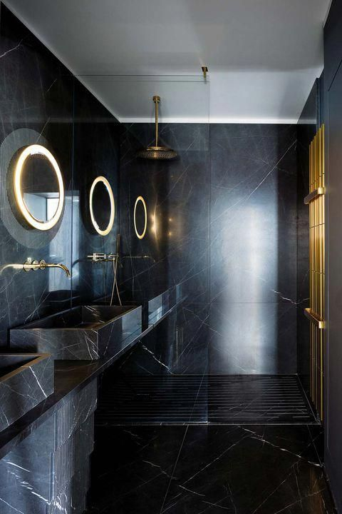a minimalist black and gold bathroom clad with black marble, with lit up mirrors, gold accessories and fixtures