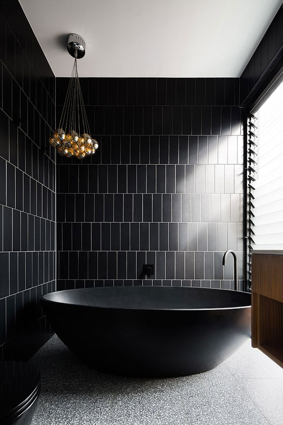 a minimalist black and gold bathroom with a stone floor, a bubble chandelier and a pretty free-standing tub