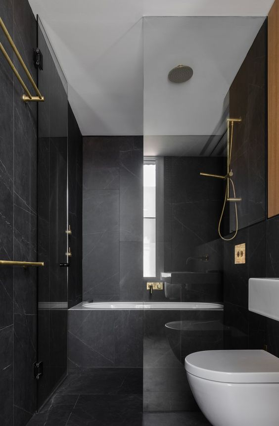 a minimalist black and gold bathroom with black marble tiles, gold fixtures and white appliances is super stylish