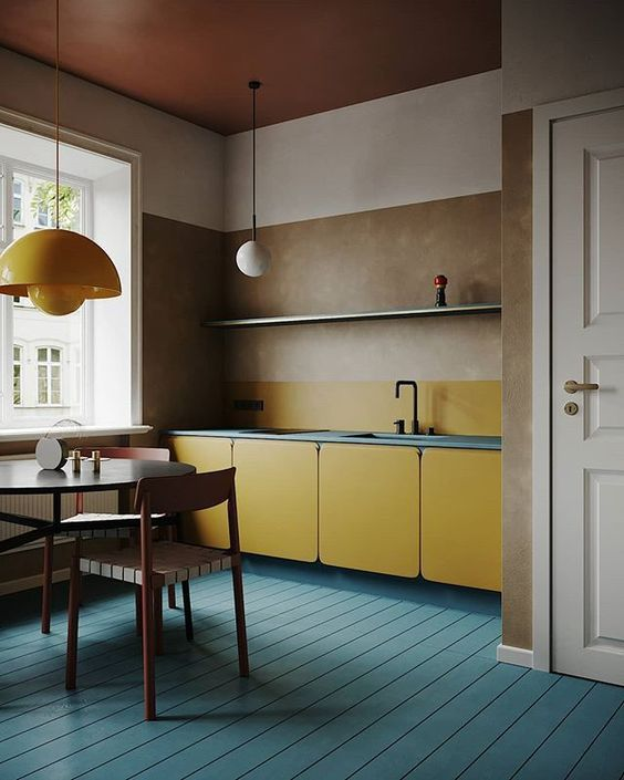 a minimalist blue and yellow kitchen with mid century modern lamps and MDF cabinets plus a cognac ceiling
