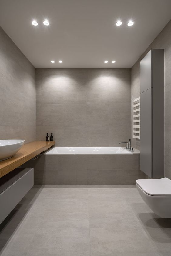 a minimalist grey and taupe bathroom clad with large scale tiles, with a sleek storage unit and a wooden vanity