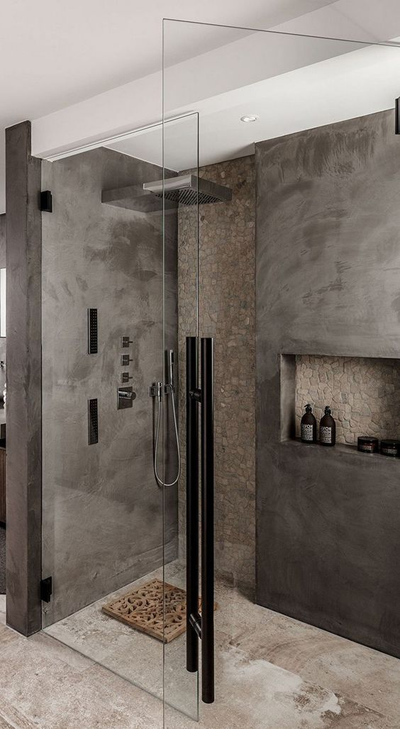 a minimalist grey and taupe bathroom done with concrete and stone, with a wooden rug and black touches