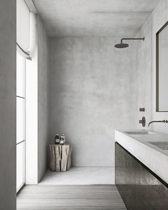 a minimalist grey bathroom clad with concrete and with greyish wood on the floor, with a large window and a black vanity