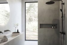 a minimalist grey bathroom clad with tiles and concrete, with a white concrete vanity and sink and black fixtures