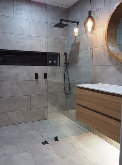 a minimalist grey bathroom clad with tiles, with a floatign vanity and a pendant lamp plus black fixtures