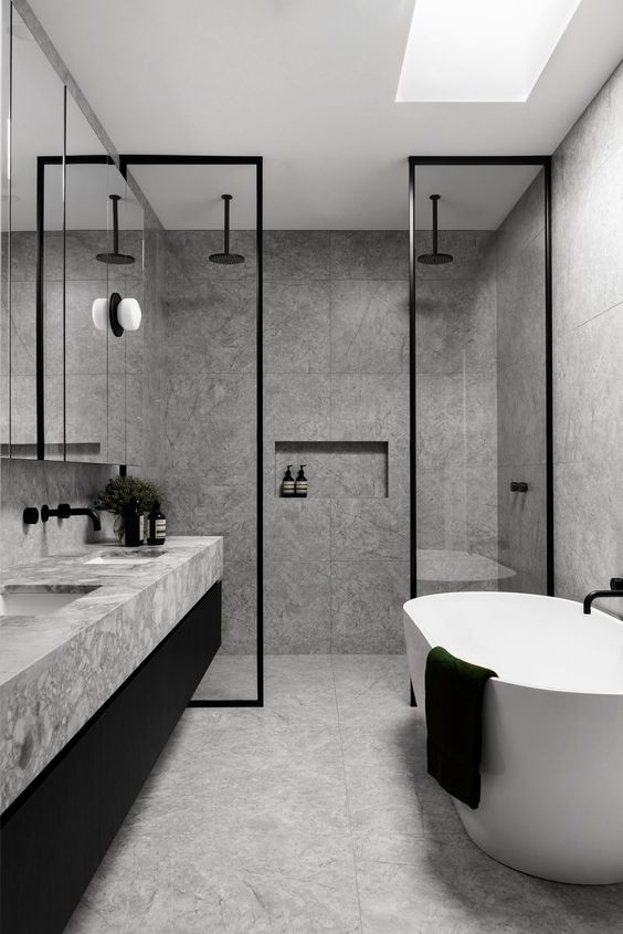 a minimalist grey bathroom done with grey marble tiles, glass doors, touches of black for drama and a skylight