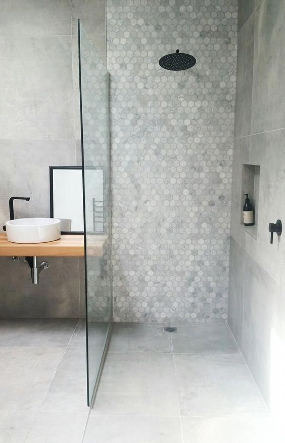 a minimalist grey bathroom done with hex and usual tiles, with a floating vanity and black fixtures