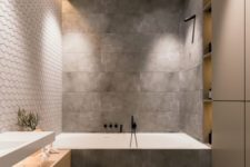 a minimalist grey bathroom done with tiles, with a large sleek storage unit and a wooden vanity plus built-in lights