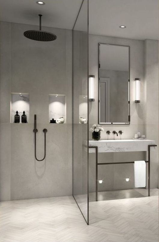 a minimalist grey bathroom done with various tiles, with a marble vanity and black framing and fixtures for a bolder look