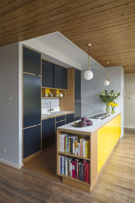 a minimalist kitchen done in navy and bright yellow, with natural wood touches and pendant lamps
