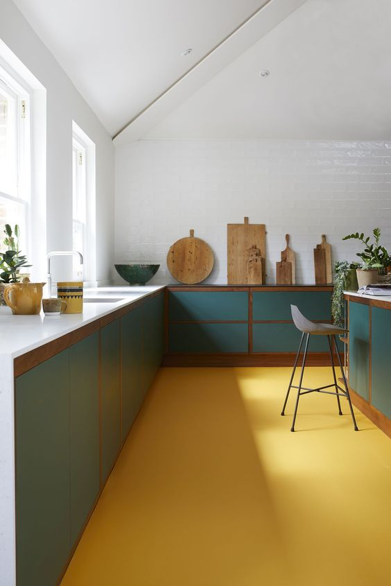 a minimalist kitchen done with a sunny yellow floor, turquoise cabinets, touches of stained wood and all white walls and ceiling