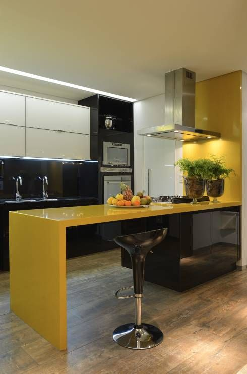 a minimalist kitchen in bold yellow and black, with glossy surfaces and lots of lights here and there