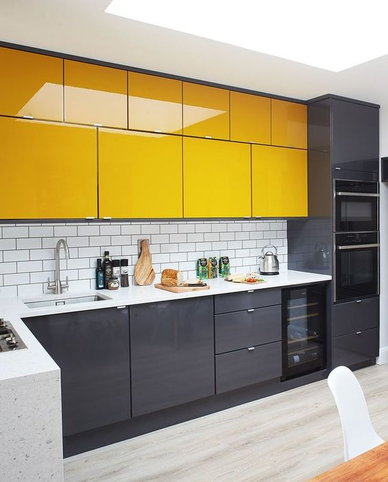 a minimalist kitchen with black lower cabinets and bright yellow upper ones plus white countertops is ultimately bold