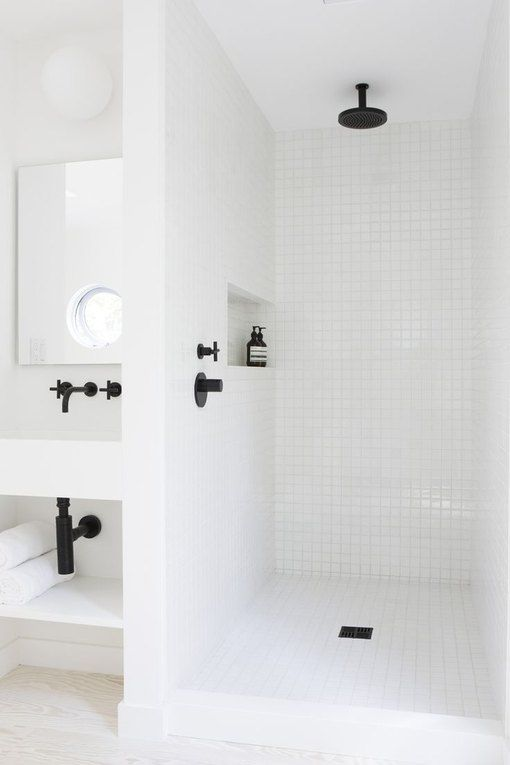 a minimalist white bathroom clad with tiles in the shower space, with black fixtures and all white everything
