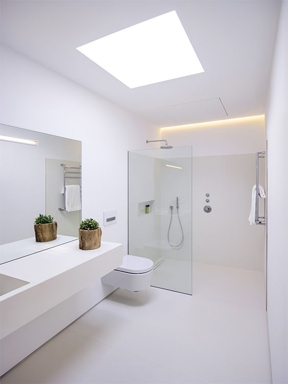 a minimalist white bathroom with a skylight, a floating vanity, a seamless glass shower space and built-in lights