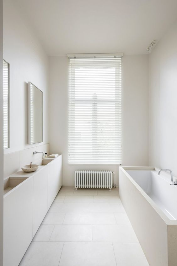 a minimalist white bathroom with a tub and sinks clad with white plywood, mirrors, a radiator and shades on the window