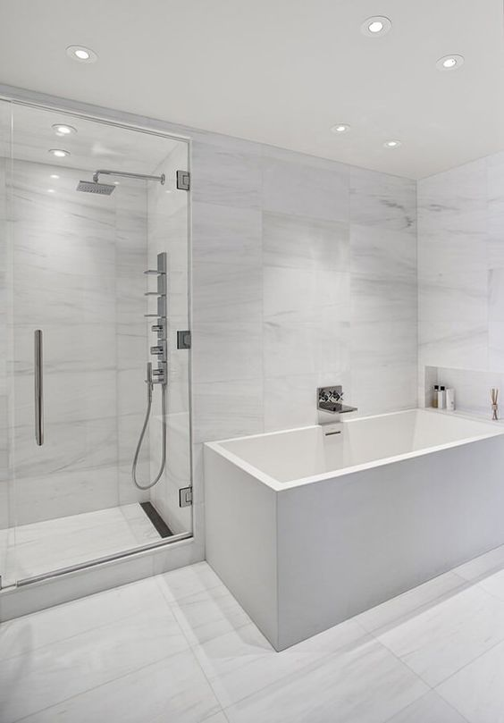 a minimalist white bathroom with marble large scale tiles, a square tub and built-in lights all over