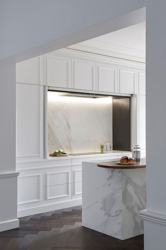 a modern and elegant white kitchen design with paneling all over, built-in appliances and a white marble backsplash