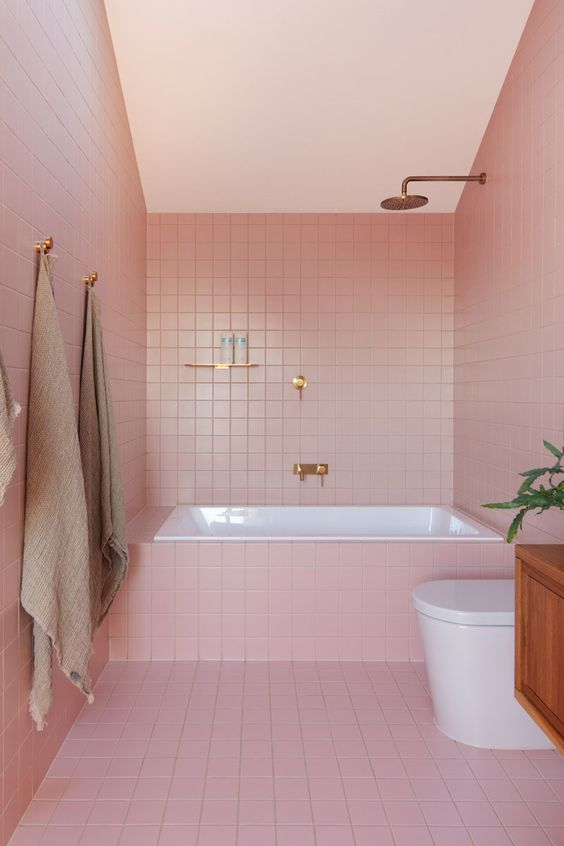 a modern glam bathroom clad with pink tiles and finished off with brass and gold fixtures for a chic look