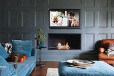 a modern luxurious living room with grey paneled walls, blue furniture and a built-in fireplace and TV