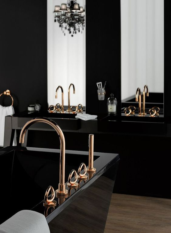 a modern refined bathroom with black sinks, a black sculptural tub, a chic blakc chandelier, gold fixtures and large mirrors