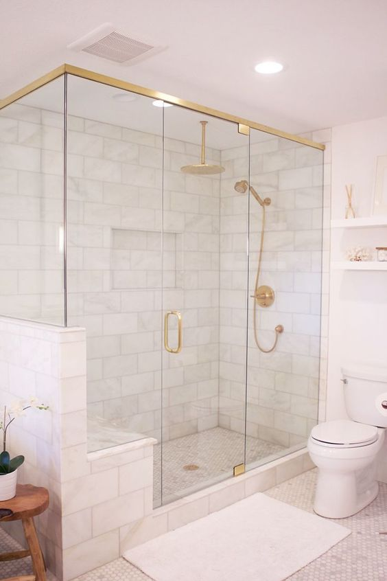 a modern white bathroom with gold framing up the shower, gold fixtures and handles and all white everything
