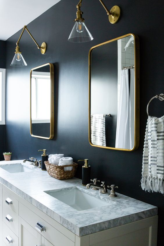 a moody bathroom with midnight blue walls, gold frame mirrors, gold sconces and other touches for more chic