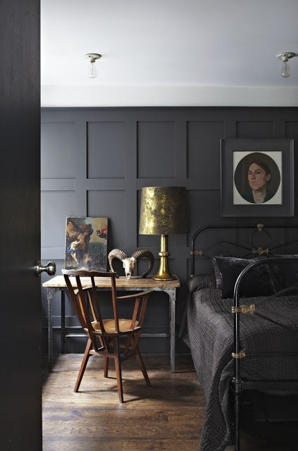 a moody bedroom with an elegant charcoal grey paneled wall, a black metal bed and vintage decor and artworks