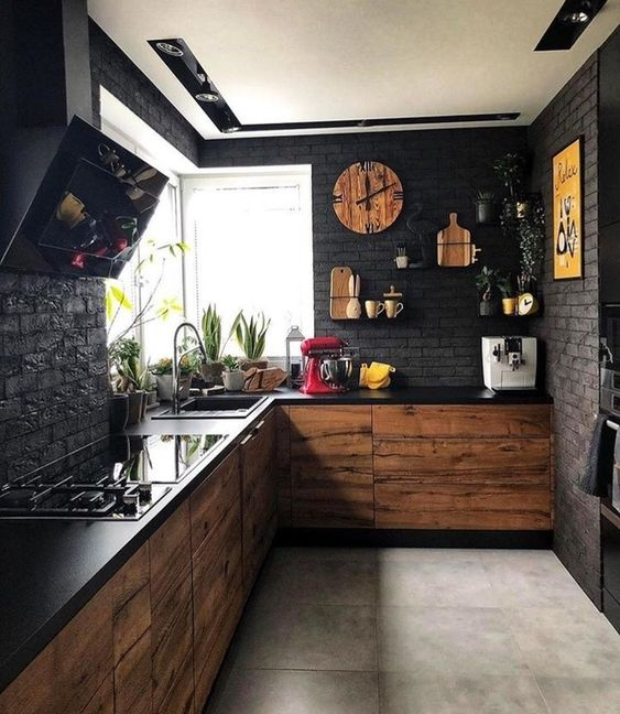 a moody black kitchen with faux brik walls, black countertops plus MDF cabinets and touches of yellow