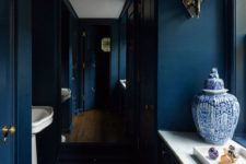 a moody navy powder room with all-navy walls, chic gold fixtures and lamps and white stone touches here and there