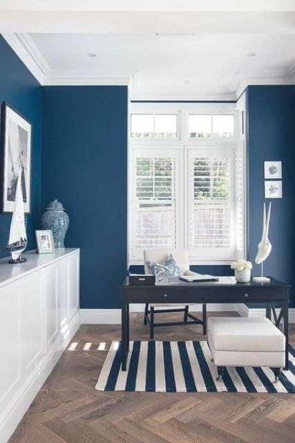 a nautical home office with navy walls, a striped rug, a black desk and a white storage unit plus white shutters and sea decor