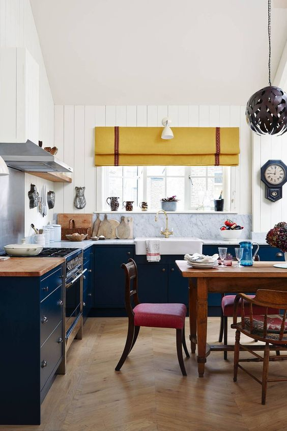 a navy and white kitchen with white stone countertops, a yellow curtain and brigth red chairs looks cool and eclectic