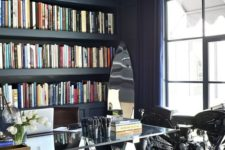 a navy home office with a coffered ceiling, built-in storage space, a glass and metal desk plus a bike as decor