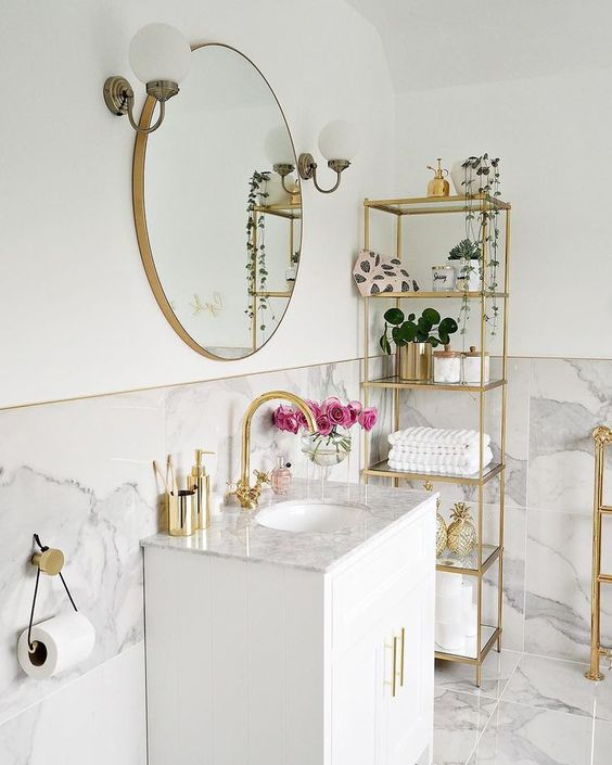 a neutral bathroom with a tall gold etagere, a matching stand and a cool sign on the wall