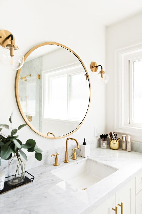 a neutral bathroom with gold fixtures, gold sconces and a round gold framed mirror plus smaller accessories in gold