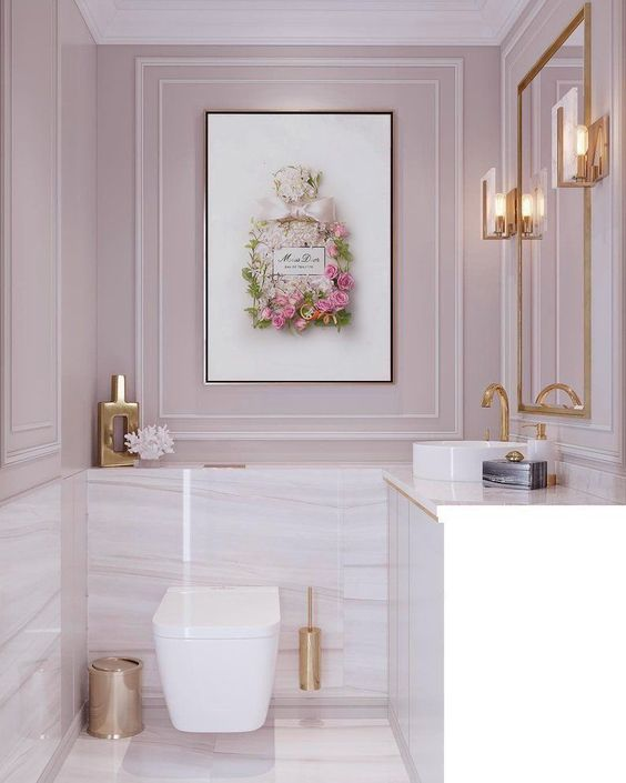 a pale pink powder room with white and pink marble tiles, gold accessories and framing for a chic and glam touch