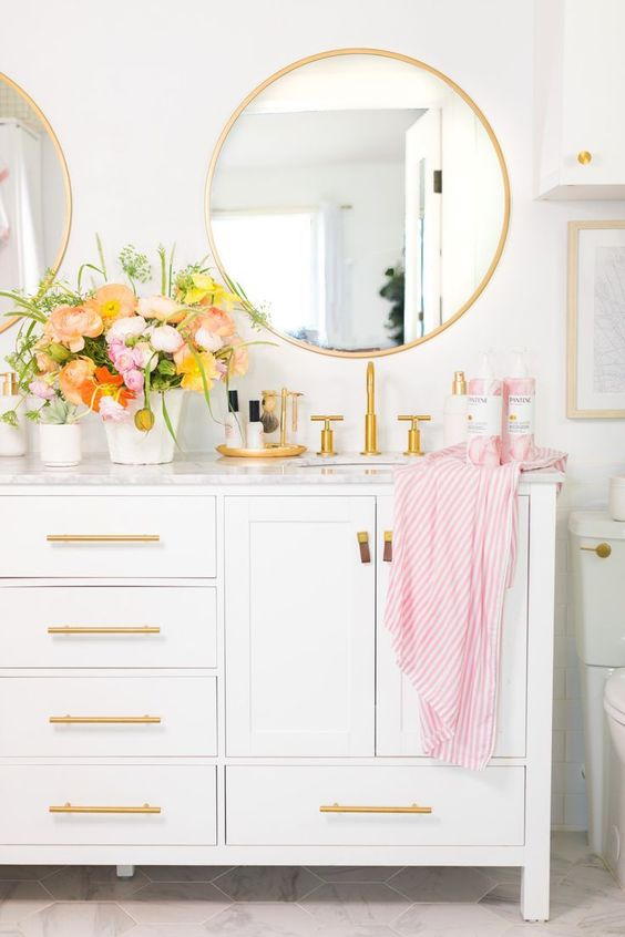 a pretty white bathroom with gold handles, gold framed mirrors and fixtures looks dreamy and very romantic