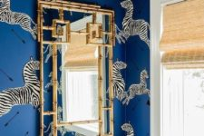 a quirky powder room with blue zebra print wallpaper, a catchy and bold chandelier, a gold frame mirror is wow