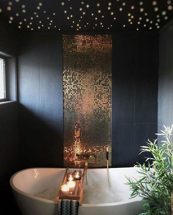 a refined bathroom with matte navy tiles, a gold tile backsplash, built-in lights and candles is a dreamy space to be