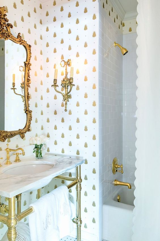 a refined bathroom with white and gold pineapple wallpaper, godl fixtures, a vanity and an exquisite mirror in a gold frame