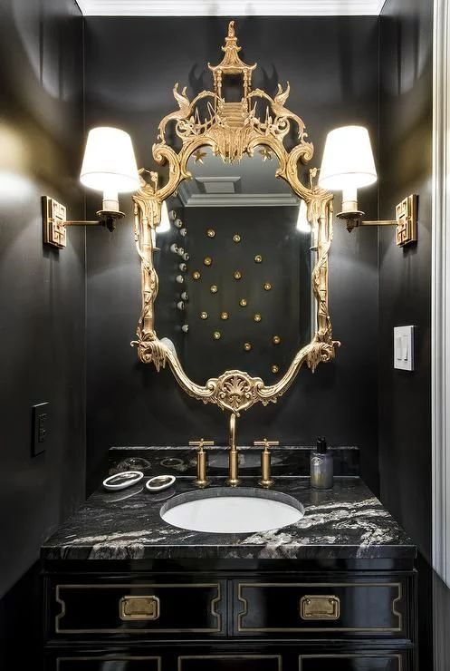 a refined black and gold bathroom with a chic ornate mirror, wall sconces, a black vanity and a white sink
