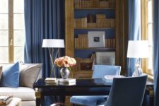 a refined blue home office with a chic black desk, blue chairs, walls and textiles and elegant touches of gold here and there