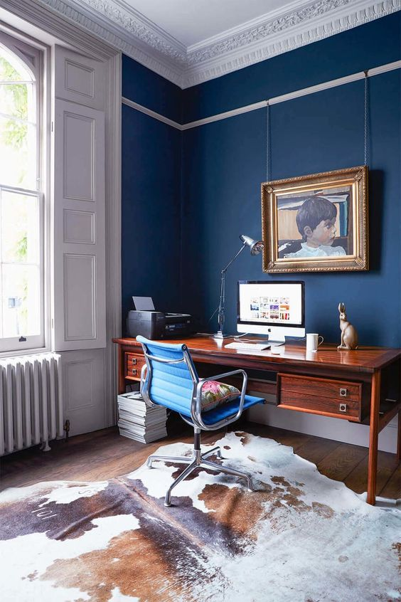 a refined blue home office with panels, a beautiful ceiling, a chic stained wooden desk, a catchy artwork