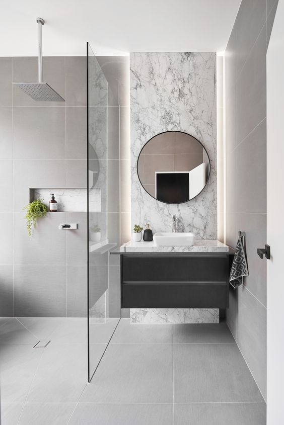 a refined grey bathroom clad with large scale tiles, with white marble and a floating vanity plus greenery