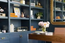 a refined home office with navy walls taken by storage units, with an acrylic and wooden desk, touches of gold for chic and style